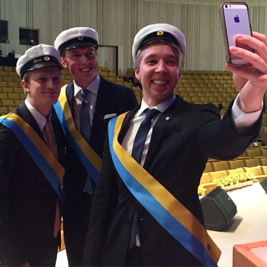 KI ushers taking a selfie and preparing for the graduation ceremony.